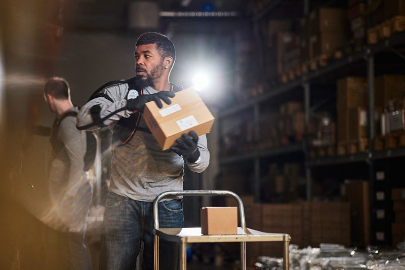 Un employé manipulant des cartons, munis du dispositif Ironhand 2.0